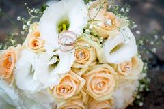 Кольца на букете свадьбы белых цветков и роз персика Стоковое Изображение