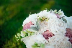 Кольца на букете цветков против предпосылки зеленой травы Стоковая Фотография RF