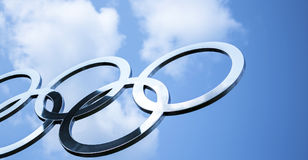 Кольца сияющей нержавеющей стали олимпийские с голубым небом Стоковое Изображение