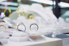 Кольца с бриллиантом и ожерелья ювелирных изделий показывают в роскошном магазине розничной торговли Стоковые Фотографии RF