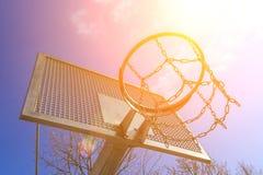 Кольцо баскетбола современного металла особопрочное на земле спорта на предпосылке голубого неба и солнца Стоковые Фотографии RF