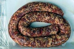 Кольцо свежей самодельной сосиски на серой предпосылке Стоковое Фото