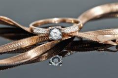 Кольцо с бриллиантом золота отдыхает на цепи с соткать змейки Стоковые Изображения