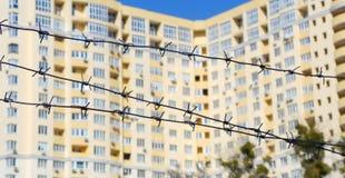 Колючая проволока вокруг незаконченного здания символизируя кризис в строительной промышленности Стоковые Изображения