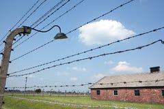 Колючая проволока и казармы в лагере Освенцим Стоковая Фотография