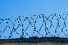 Колючая проволока на загородке с голубым небом Тюрьма, спасение, беженец, стоковое фото