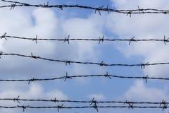 Колючая проволока против голубого неба Голубое небо покрыто с колючей проволокой Тюрьма и голубое облачное небо стоковая фотография