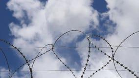 Колючая проволока против голубого неба с белыми облаками сток-видео