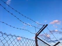 Колючая проволока na górze железной загородки против голубого неба Стоковые Изображения