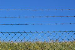 Колючие провод и загородка металла против голубого неба 2 Стоковое Фото