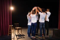 Команда актеров формируя их штабелированные руки стоковые изображения rf