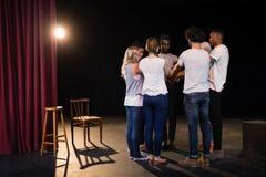 Команда актеров формируя их штабелированные руки стоковое изображение