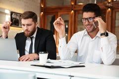 Команда бизнесмена работая в офисе, говоря на мобильном телефоне, usi Стоковые Фото
