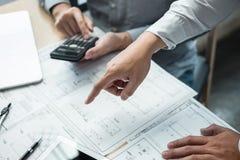 Команда встречи инженерства или архитектора и обсуждать на светокопии и строя модели пока проверяющ информацию на делать эскиз к стоковая фотография rf