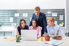 Команда дела в современном ярком интерьере офиса на работе на компьтер-книжке Стоковая Фотография