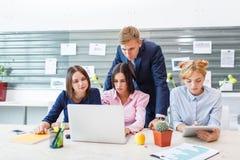 Команда дела в современном ярком интерьере офиса на работе на компьтер-книжке Стоковые Изображения