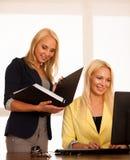 Команда дела - 2 женщины работают в офисе проверяя базу данных Стоковое Изображение RF