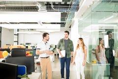 Команда дела идя и говоря в офисе Стоковые Изображения