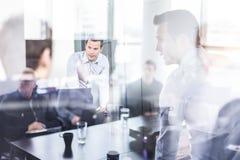 Команда дела коллективно обсуждать на встрече в современном корпоративном офисе стоковое изображение