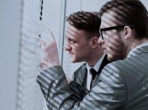 Команда дела нажимая шторки и смотря вне ветер офиса Стоковые Фотографии RF