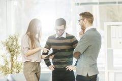 Команда дела обсуждая рабочие планы в лобби современного офиса Стоковые Изображения