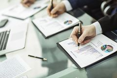 Команда дела работает с финансовыми план-графиками в рабочем месте в офисе Стоковые Фото
