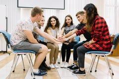 Команда дела сидя в круге на предпосылке офиса Люди показывая единство Принципиальная схема общины Стоковые Изображения