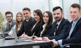 Команда дела сидя на столе в конференц-зале Стоковые Фотографии RF