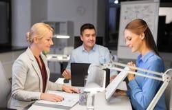 Команда дела с бумагами работая поздно на офисе стоковая фотография rf