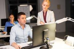 Команда дела с деятельностью компьютера поздно на офисе стоковое изображение