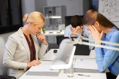 Команда дела с деятельностью ноутбука поздно на офисе стоковые изображения