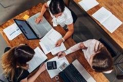 Команда женских бухгалтеров подготавливая ежегодный финансовый отчет работая с бумагами используя компьтер-книжки сидя на столе в Стоковые Фото