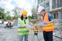 Команда инженеров нося желтый шлем и работая на строительной площадке стоковая фотография rf