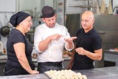 Команда кондитеров говоря о рецепте круассана стоковая фотография