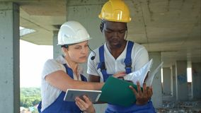 Команда конструкции советует с и рассматривает планами для конструкции стоковая фотография