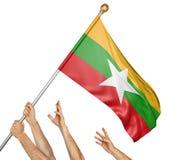 Команда людей вручает поднимать Мьянму, национальный флаг Стоковые Фото