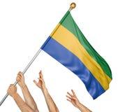 Команда людей вручает поднимать национальный флаг Габона Стоковые Изображения