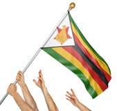 Команда людей вручает поднимать национальный флаг Зимбабве Стоковая Фотография