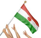 Команда людей вручает поднимать национальный флаг Нигера Стоковое Изображение