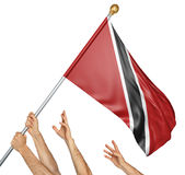 Команда людей вручает поднимать национальный флаг Тринидад и Тобаго Стоковые Изображения RF
