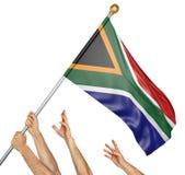 Команда людей вручает поднимать национальный флаг Южной Африки Стоковое фото RF