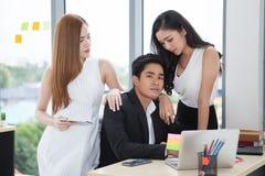 команда молодого бизнесмена и 2 коммерсанток работая вместе с ноутбуком на столе в офисе casanova босса и стоковая фотография rf