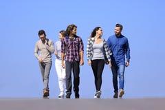 Команда молодые люди идя вдоль дороги outdoors Стоковые Изображения