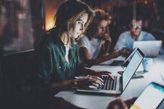 Команда молодых сотрудников работая совместно на офисе ночи Молодая женщина используя передвижную компьтер-книжку на таблице гори Стоковое фото RF