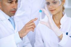 Команда научных исследователей в лаборатории изучая вещества или пробу крови Новая вакцина для industr лекарствоведения Стоковая Фотография RF
