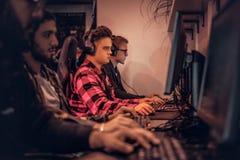 Команда подростковых gamers играет в предназначенной для многих игроков видеоигре на ПК в клубе игры стоковое фото rf