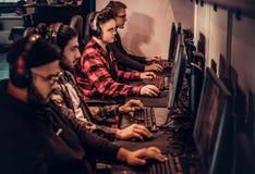 Команда подростковых gamers играет в предназначенной для многих игроков видеоигре на ПК в клубе игры стоковые изображения rf