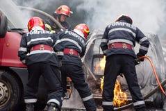 Команда пожарных разбирает автомобиль на огне стоковые фото