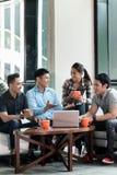Команда 4 преданных работников работая совместно стоковые фотографии rf