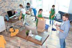 Команда привратников в равномерном офисе чистки стоковые фотографии rf